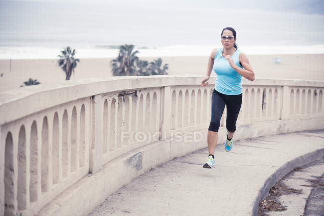 Woman running up sidewalk by beach — Stock Photo
