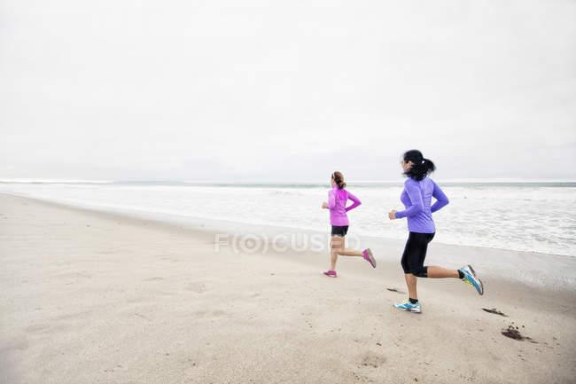 Corredores treinando juntos na areia — Fotografia de Stock