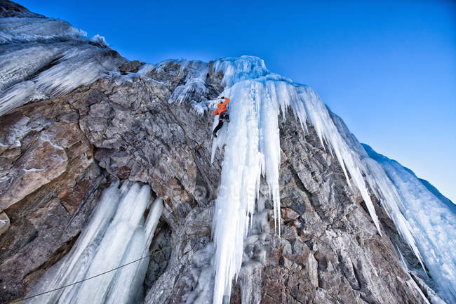 Ice climber ascending frozen waterfall — стоковое фото