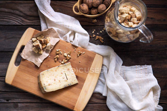 Cheese with croutons and walnuts on table — Stock Photo