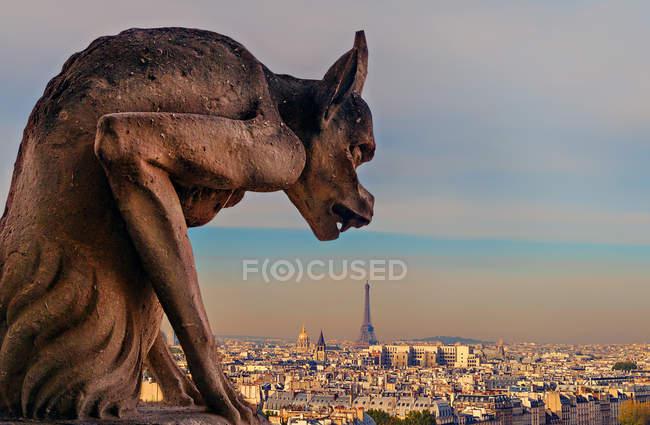 Gargoyle on Notre Dame with view of Paris — Stock Photo
