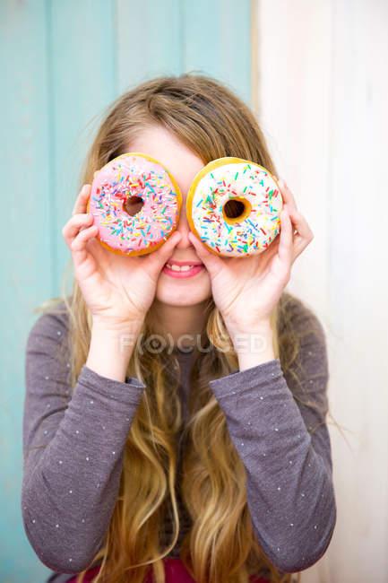 Chica mirando a través de donuts - foto de stock