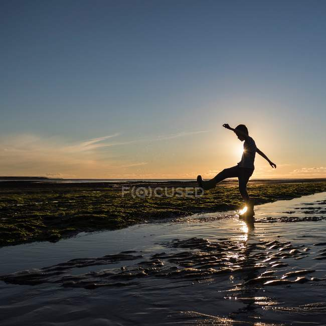 Little boy kicking water at beach — Stock Photo