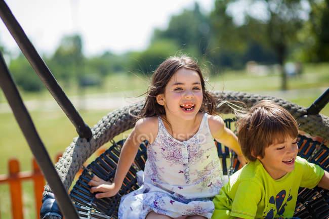 Happy children on swing — Stock Photo