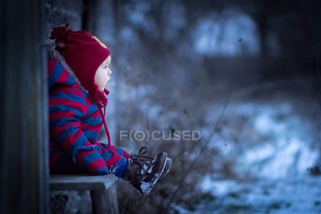 Хлопчик, сидячи на лавці за межами — стокове фото