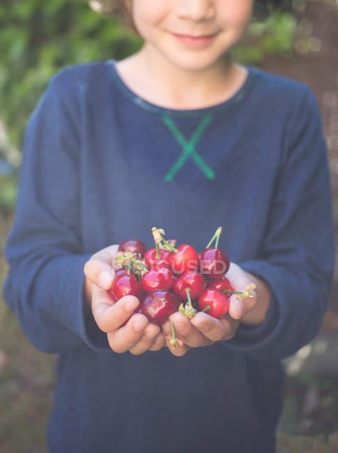 Girl with handful of cherries — Stock Photo