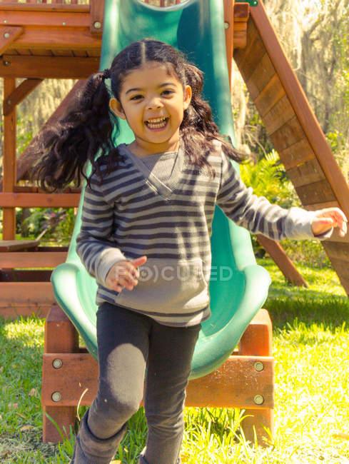 Девушка смеется приходя вниз слайд — стоковое фото