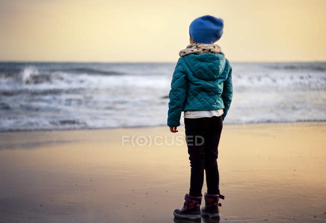 Ragazza in piedi sulla spiaggia — Foto stock