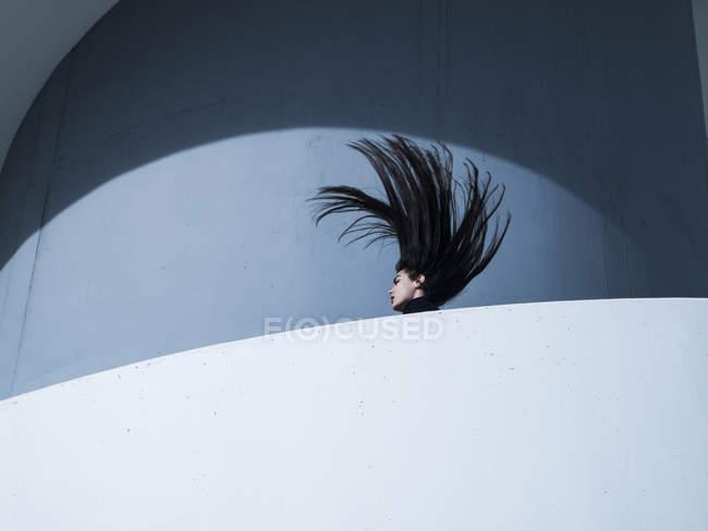 Jeune femme jetant sa tête en arrière — Photo de stock