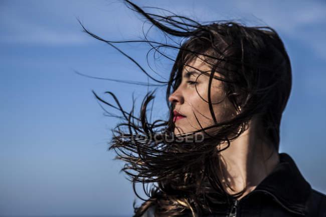 Jeune femme aux cheveux souffler le vent — Photo de stock
