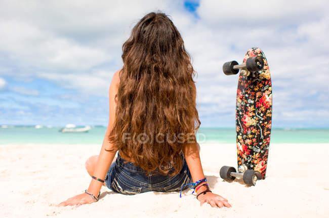 Girl sitting on sandy beach with skateboard — Stock Photo
