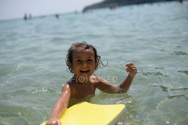 Усміхаючись дівчинка, граючи з float — стокове фото