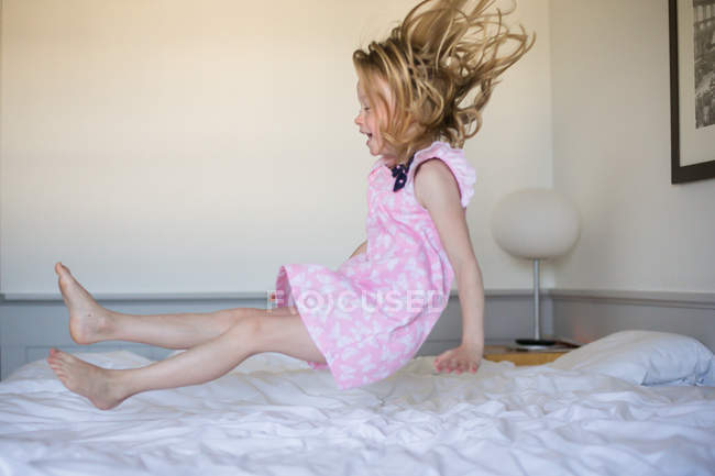 Girl bouncing on bed — Stock Photo