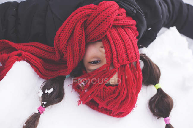 Girl with red scarf covering face — Stock Photo