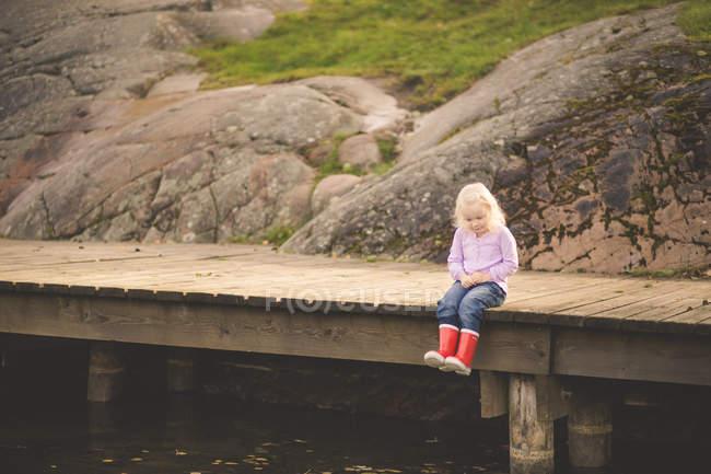 Girl sitting on wooden pier — Stock Photo