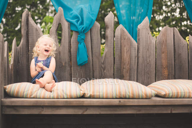 Girl sitting on bench laughing — Stock Photo