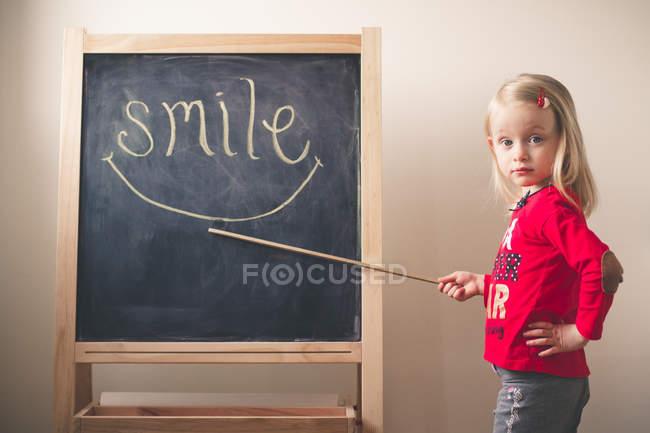 Маленькая девочка, указывающая на улыбку слова — стоковое фото