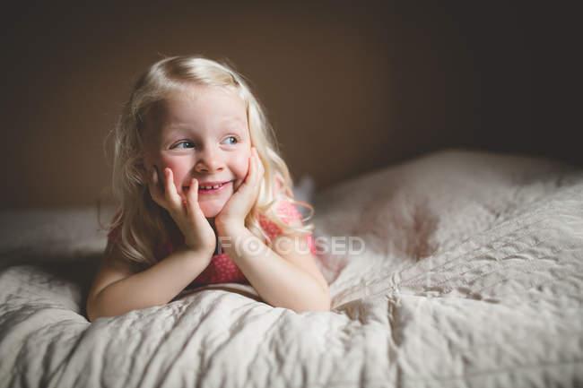 Sorridente garota deitada na cama — Fotografia de Stock
