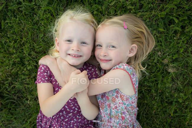 Zwei Mädchen, die sich auf dem Gras umarmen — Stockfoto