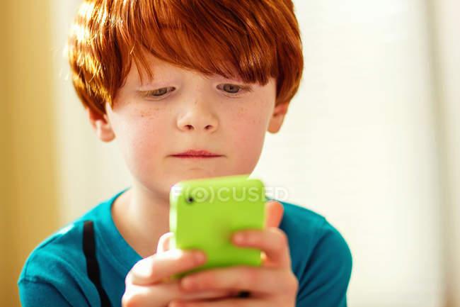 Young boy playing mobile game — Stock Photo