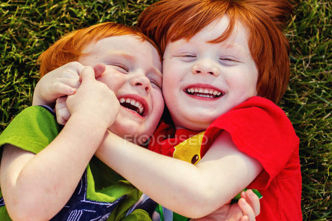 Brothers playing in grass — Stock Photo