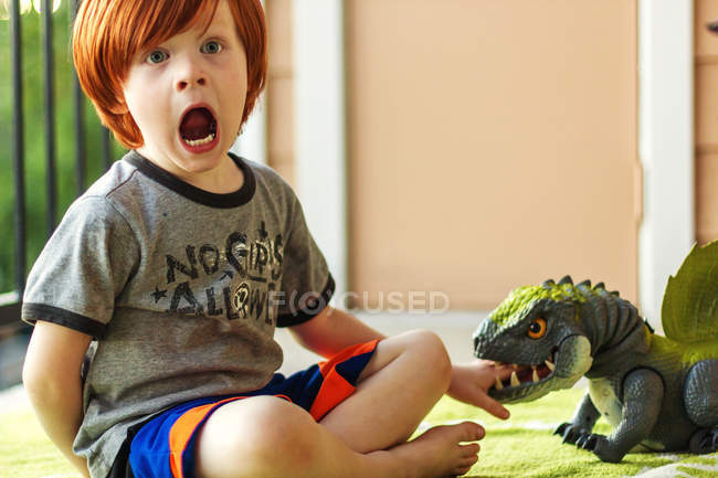 Young boy playing with toy dinosaur — Stock Photo