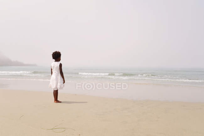 Girl at beach looking out to sea — Stock Photo