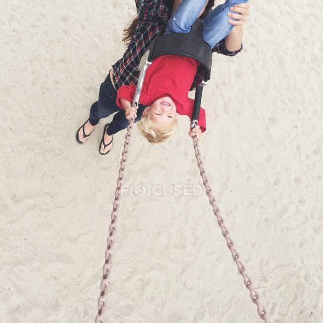 Donna spingendo suo figlio su swing — Foto stock