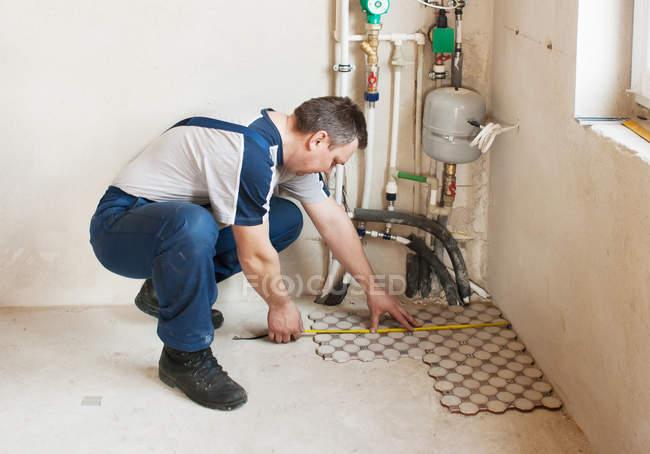 Uomo posa piastrelle del pavimento in casa nuova u foto stock