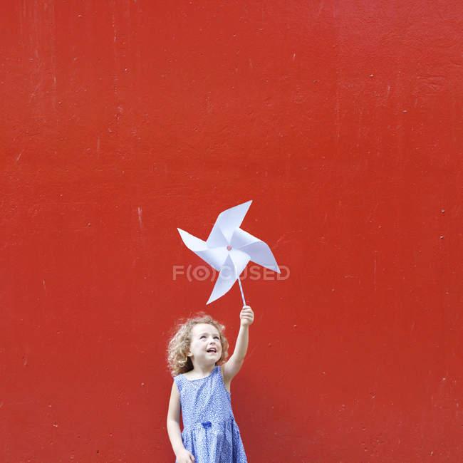 Smiling girl holding pinwheel — Stock Photo