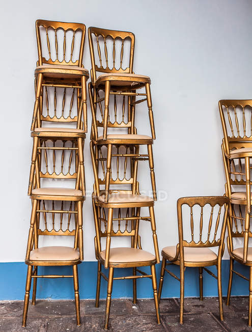 Stacks of gold ballroom chairs — Stock Photo