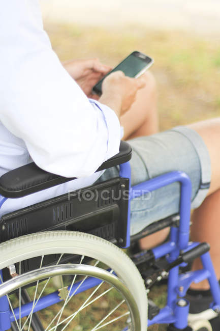 Man in wheelchair using mobile phone — Stock Photo