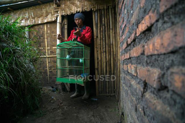 Tenggerese Man holding a bird cage — Stock Photo