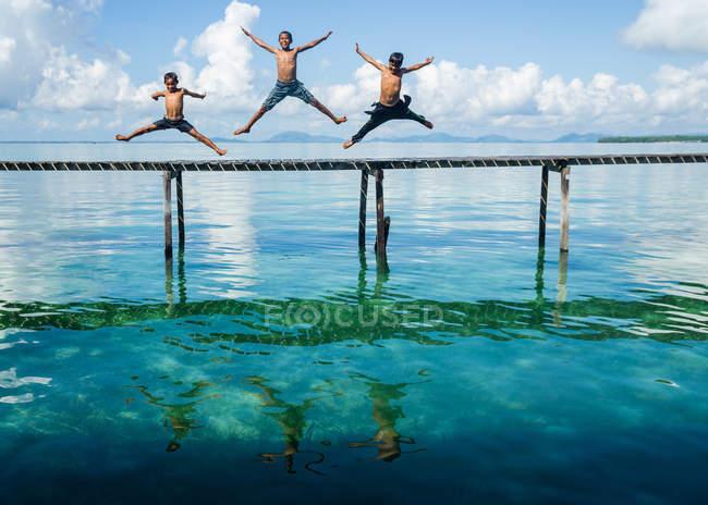 Chicos saltando al mar desde el embarcadero - foto de stock