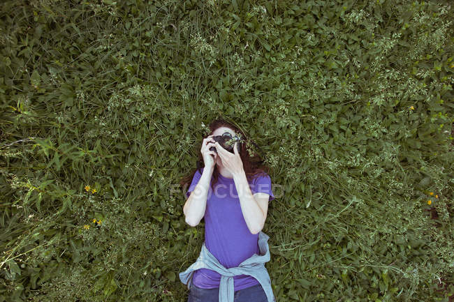 Женщина лежит в зеленой траве — стоковое фото