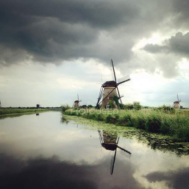 Molinos de viento por río, Kinderdijk , - foto de stock