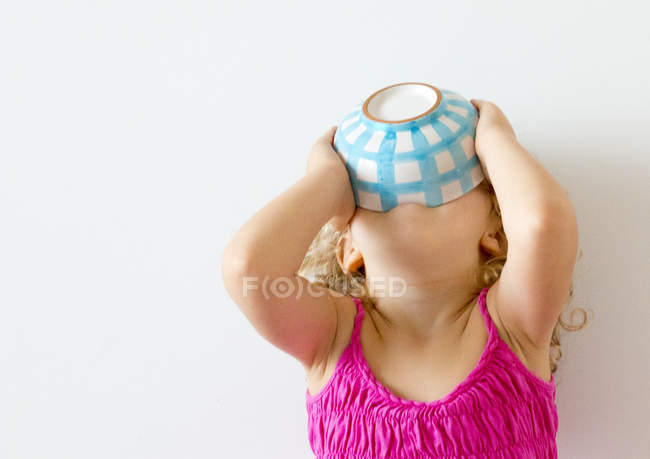 Girl holding cereal bowl to mouth — Stock Photo