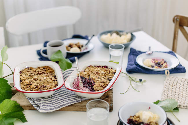 Table laid with blueberry crumble — Stock Photo