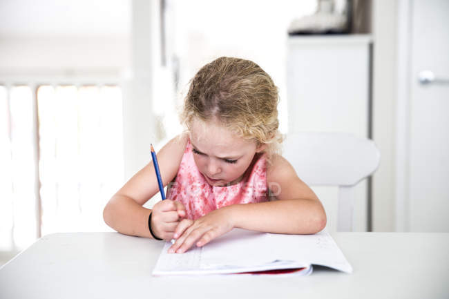 Girl rubbing out homework — Stock Photo