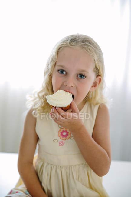 Chica comiendo cupcake de limón - foto de stock