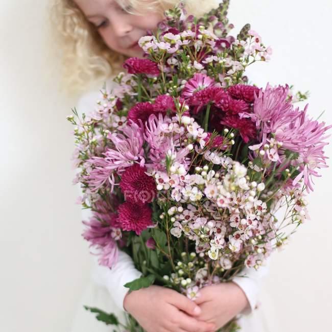 Mädchen mit großem Strauß rosa Blumen — Stockfoto