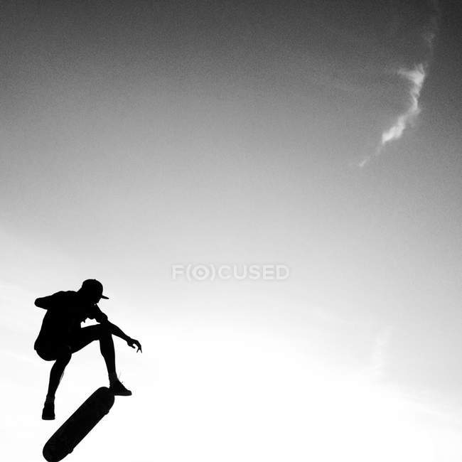 Silhouette of a skateboarder in jump — Stock Photo