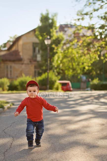 Bébé garçon courant dans la rue — Photo de stock