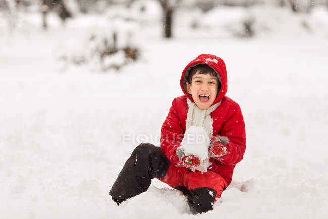 Boy sitting in snow with snowball — Stock Photo