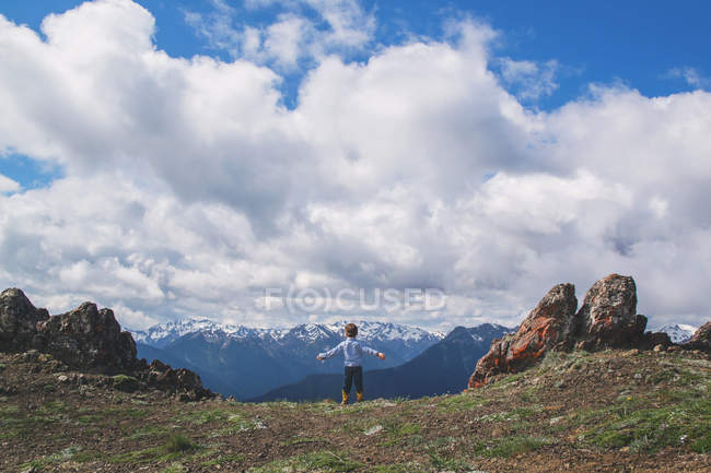Boy standing on cliff — Stock Photo