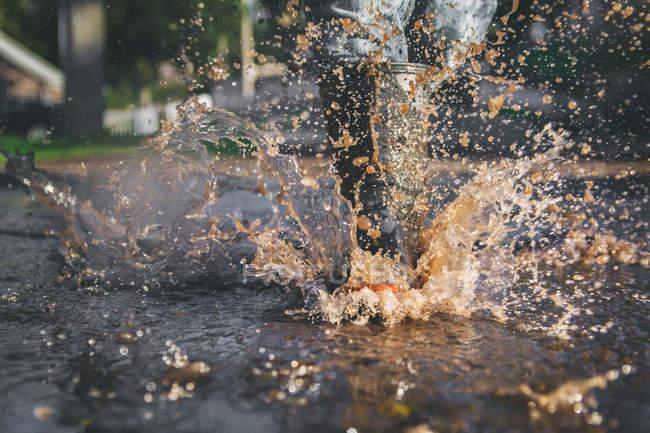 Child legs splashing in puddle — Stock Photo