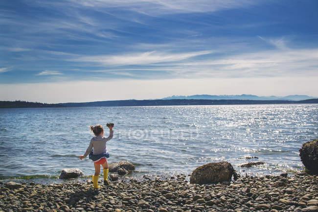 Jeune fille jetant des rocher dans la mer — Photo de stock