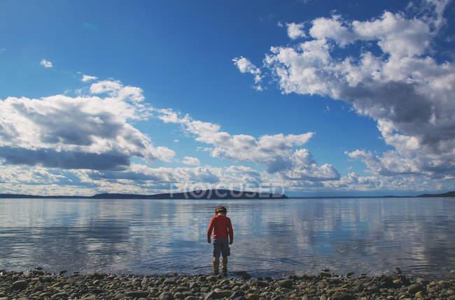 Niño de pie en el borde del agua - foto de stock