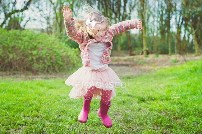 Menina pulando no ar no parque — Fotografia de Stock