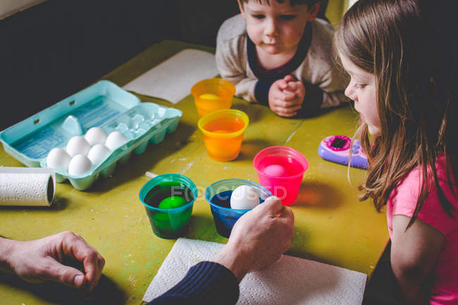 Children dyeing Eeaster eggs — Stock Photo
